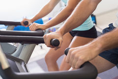 Mid section of couple working on exercise bikes at gym Royalty Free Stock Photography