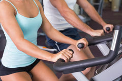 Mid section of couple working on exercise bikes at gym Royalty Free Stock Photos