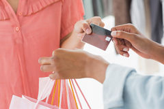 Mid section of customer receiving shopping bags and credit card from saleswoman Stock Image