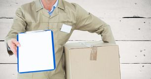 Mid section of delivery man with box and clipboard Stock Images