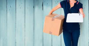 Mid section of delivery woman holding parcel box and clipboard Royalty Free Stock Images
