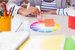 Mid section of designer with color samples at desk Stock Image
