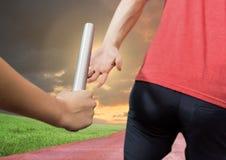 Mid-section die van atleet de knuppel overgaan tot teammate in stadion bij zonsondergang Royalty-vrije Stock Fotografie