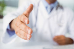 Mid section of doctor offering handshake Royalty Free Stock Images