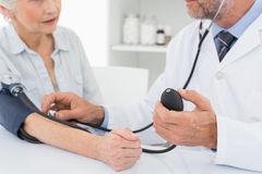 Mid section of doctor taking blood pressure of his patient Stock Photography