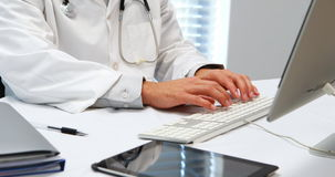 Mid-section of doctor typing on keyboard stock video footage