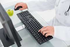 Mid section of doctor using computer Stock Image