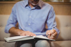 Mid section of doctor writing in organizer. In clinic Royalty Free Stock Photography