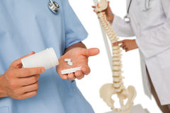 Mid section of doctors with pills and skeleton model Stock Images