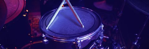 Mid section of drummer at concert. Mid section of drummer performing at concert in nightclub Stock Image