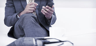 Mid section of an elegant businessman text messaging Stock Photo