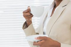 Mid section of elegant businesswoman with tea cup in office Stock Photography