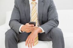 Mid section of an elegant young businessman text messaging Stock Photo