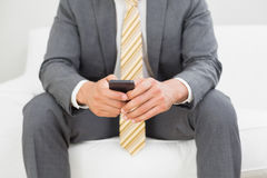 Mid section of an elegant young businessman text messaging Stock Image