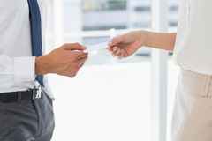 Mid section of executives exchanging business card. Side view mid section of two executives exchanging business card royalty free stock images