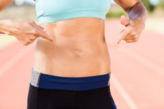 Mid section of female athlete pointing on her belly. On running track Stock Photography