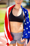 Mid section of female athlete wrapped in american flag on running track. In stadium Royalty Free Stock Image