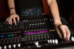 Mid-section of female audio engineer using sound mixer. In recording studio Stock Photos