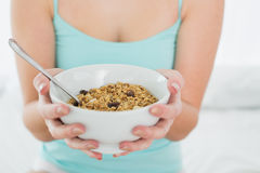 Mid section of a female with a bowl of cereal in bed Royalty Free Stock Photo
