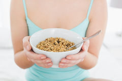 Mid section of a female with a bowl of cereal sitting on bed Stock Photos