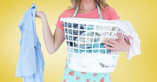 Mid section of female cleaner holding laundry basket filled with clothing. Against yellow background Royalty Free Stock Images