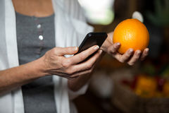 Mid section of female costumer holding orange while using mobile phone. In supermarket royalty free stock photography