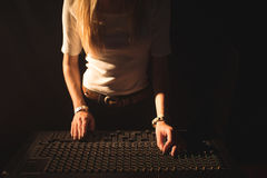 Mid section of female DJ operating sound mixer Royalty Free Stock Images
