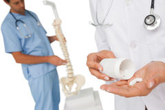 Mid section of female doctor with pills and skeleton model Stock Photo