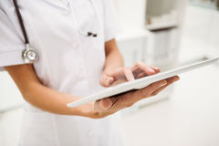 Mid section of female doctor using digital tablet in medical office Royalty Free Stock Photo