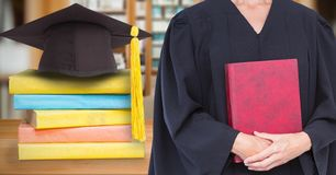 Mid section of female graduate holding red diary while standing by mortar board and stack of books Stock Photo