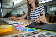 Mid section of female graphic designer using graphics tablet at desk. In office royalty free stock photography