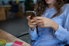 Mid section of female graphic designer using mobile phone. In office stock photography