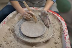 Mid section of female potter molding plate with hand tool Royalty Free Stock Photography