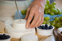 Mid section of female staff slicing cheese at counter. Of supermarket Royalty Free Stock Photography