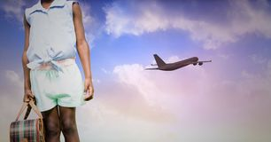 Mid section of female tourist with airplane at distance. In the sky royalty free stock photos