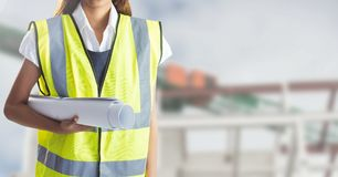 Mid section of female worker holding blue prints. Against construction site in background Royalty Free Stock Photos