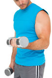 Mid section of a fit man exercising with dumbbells Stock Photography