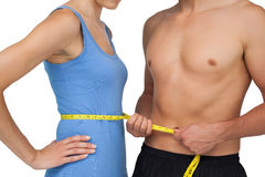 Mid section of a fit man measuring womans waist Stock Photos