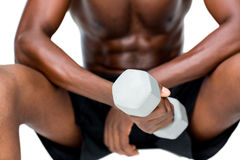Mid section of fit shirtless man lifting dumbbell Stock Image