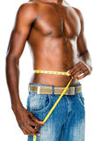 Mid section of a fit shirtless man measuring waist Stock Photography
