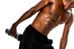 Mid section of fit shirtless young man lifting dumbbell Royalty Free Stock Photos