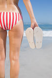 Mid section of fit woman in bikini on the beach holding flip flops Stock Photography