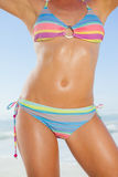 Mid section of fit woman in bikini on the beach. On a sunny day Royalty Free Stock Photography