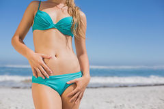 Mid section of fit woman in bikini on the beach. On a sunny day Stock Image