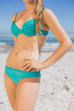 Mid section of fit woman in bikini on the beach. On a sunny day Royalty Free Stock Photo