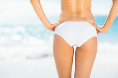 Mid section of fit woman in bikini on beach Royalty Free Stock Photo