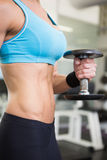 Mid section of fit woman exercising with dumbbell in gym Stock Image