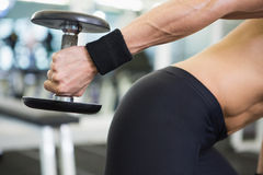 Mid section of fit woman exercising with dumbbell in gym Royalty Free Stock Photography