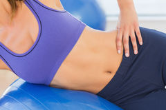 Mid section of a fit woman exercising with fitness ball Stock Image