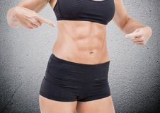 Mid section of fit woman pointing her abdomen Stock Image
